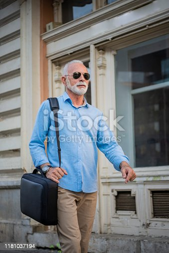 636248376istockphoto Senior Businessman is Walking in the City Streets 1181037194