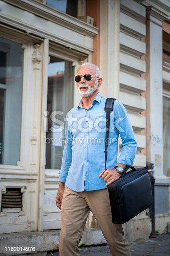 636248376istockphoto Senior Businessman is Walking in the City Streets 1182014976