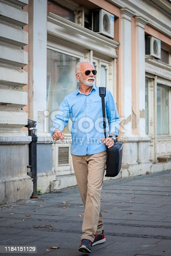 636248376istockphoto Senior Businessman is Walking in the City Streets 1184151129