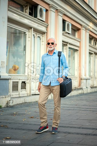 636248376istockphoto Senior Businessman is Walking in the City Streets 1188395003