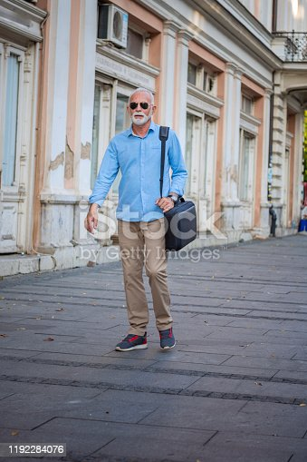 636248376istockphoto Senior Businessman is Walking in the City Streets 1192284076