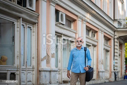 636248376istockphoto Senior Businessman is Walking in the City Streets 1193058540