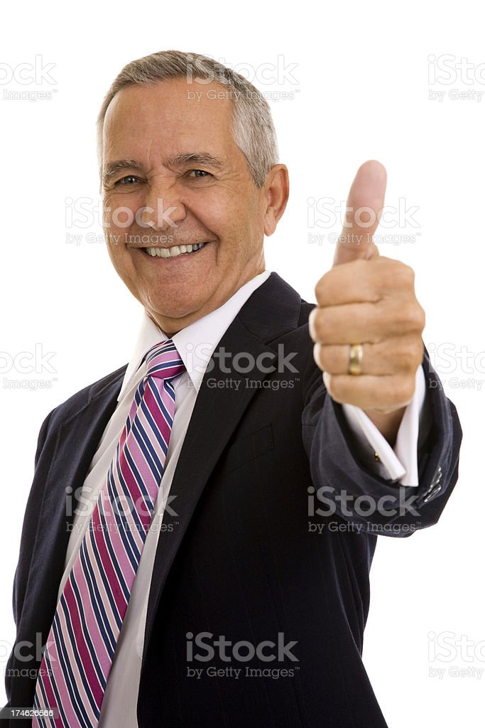 Senior businessman looking at camera gesturing thumbs up royalty-free stock photo