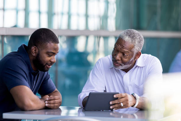 Senior businessman meets with male colleauge A senior African American businessman shows a male colleague something on a digital tablet while sitting outside on an office patio. grounds stock pictures, royalty-free photos & images