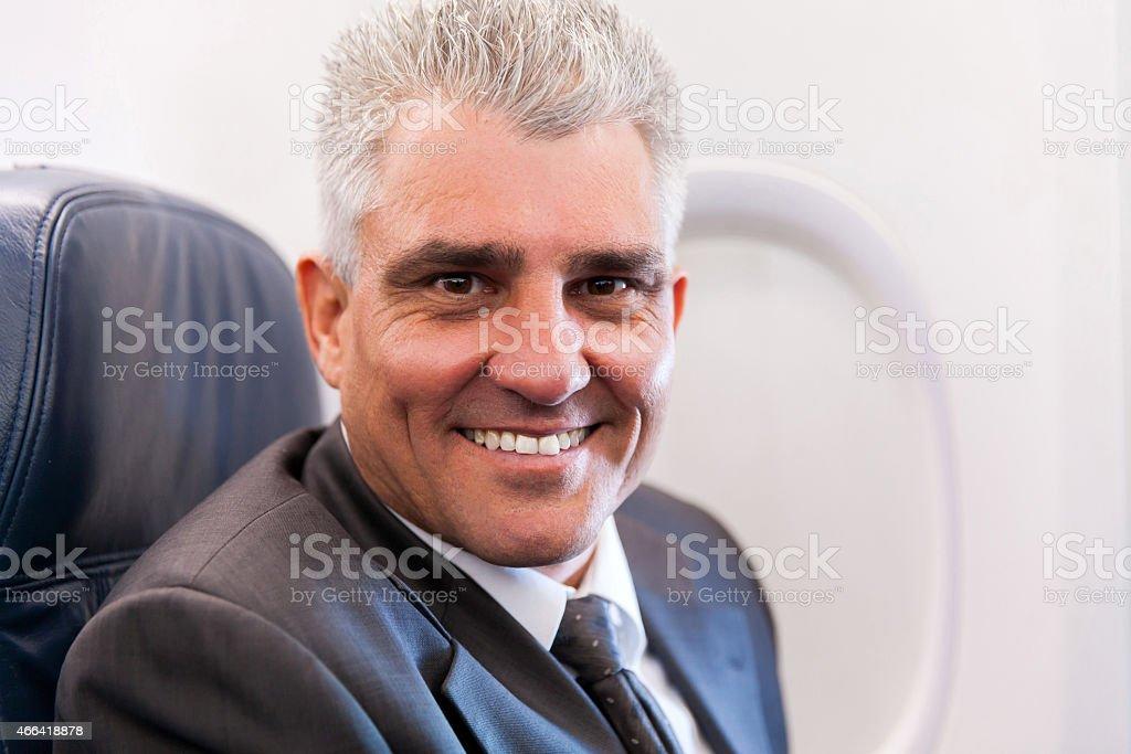 senior businessman on airplane stock photo