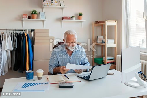 Portrait of Handsome Active Senior Businessman Working in an Office at Home. Caucasian Elderly Male Working From Home Office.