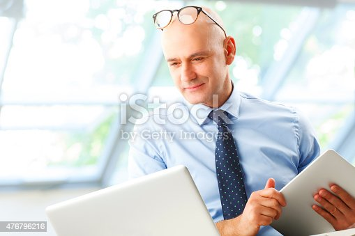 Senior businessman portrait. Portrait of financial manager sitting in front of laptop and calculating financial data.