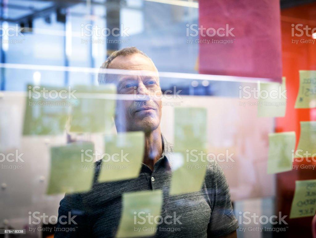 Leitenden Geschäftsmann Klebstoff Notenlesen auf Glas – Foto
