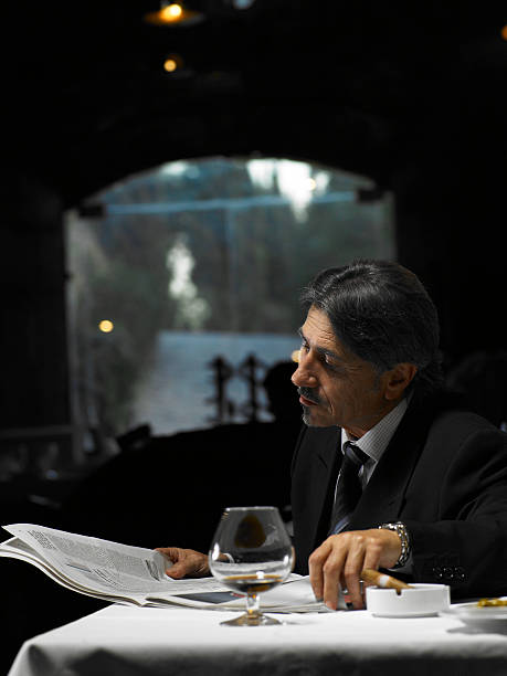 Senior businessman reading newspaper in restaurant stock photo