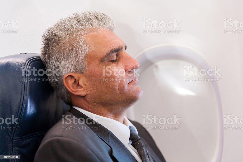 senior businessman resting on airplane stock photo