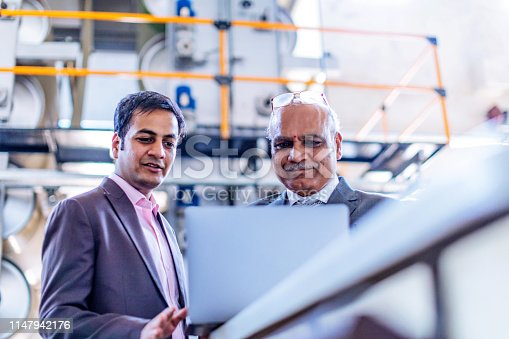 Business, India, Factory - Senior Businessman Reviewing Production Progress Report on a Laptop at the Factory Floor with his manager.