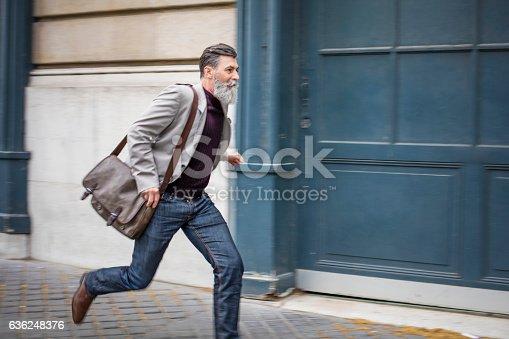 istock Senior businessman running on city street 636248376