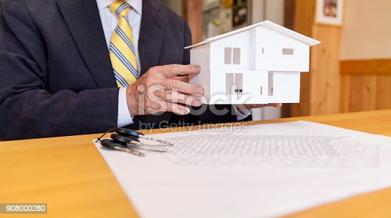 istock Senior Businessman Showing Small Model House 908000280