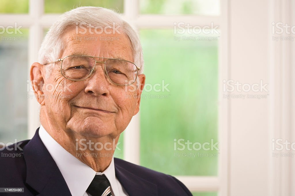 senior businessman, sitting in executive chair, looking at camera royalty-free stock photo