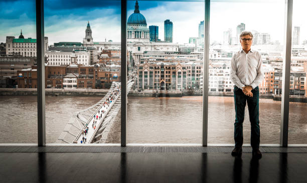 de9ff3b4fbf Senior Businessman Standing On Top Floor Of Office Building Overlooking  Modern London Urban Skyline Stock Photo   More Pictures of 1950-1959