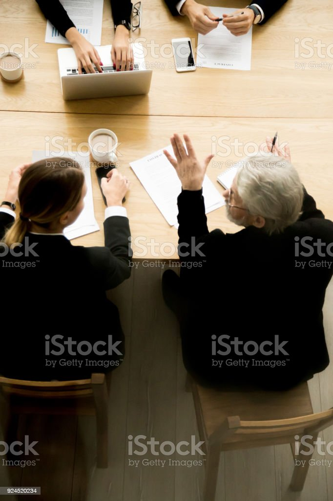 Senior businessman talking at group contract negotiations, vertical top view stock photo
