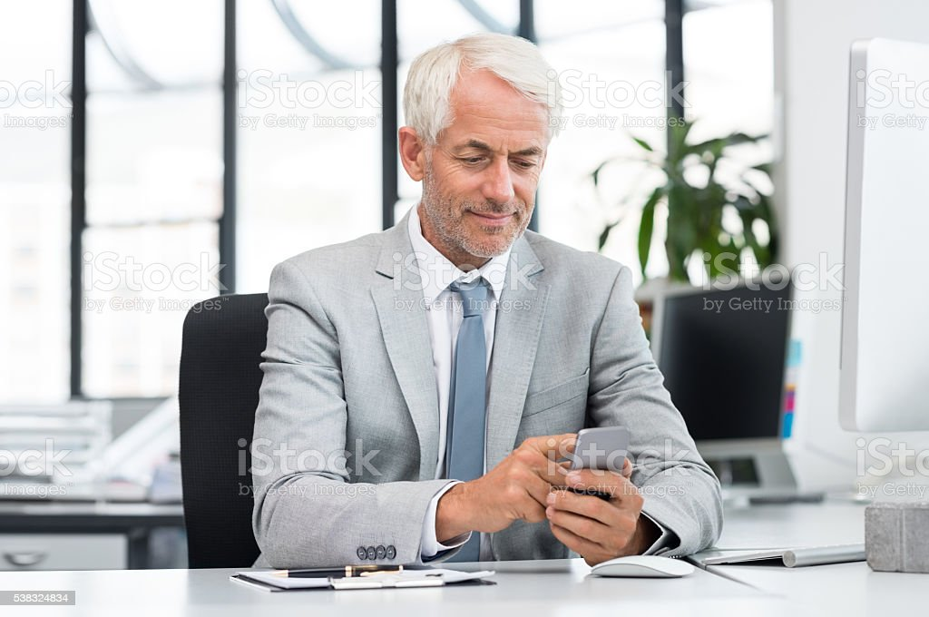 Senior businessman texting with cellphone stock photo