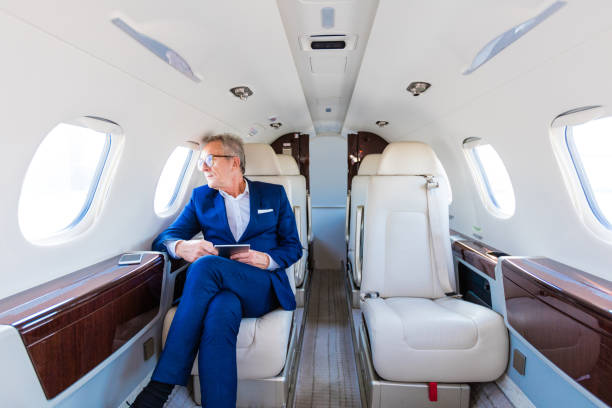 Senior businessman traveling by corporate jet stock photo