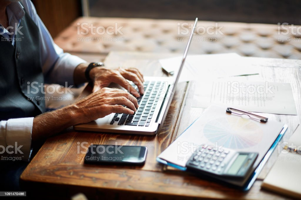 Senior businessman typing on a laptop in a coworking space Elderly unrecognizable entrepreneur using a laptop. Mobile phone, a calculator, a pie chart and some papers and notes are on the table. Accountancy Stock Photo
