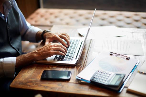 coworking uzayda bir dizüstü bilgisayarda yazarak üst düzey iş adamı - sadece yaşlı bir adam stok fotoğraflar ve resimler