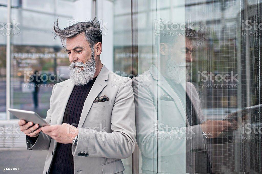 Senior hombre de negocios usando tableta digital en edificio de oficinas - foto de stock