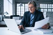 istock Senior businessman using laptop in the office 1210553230