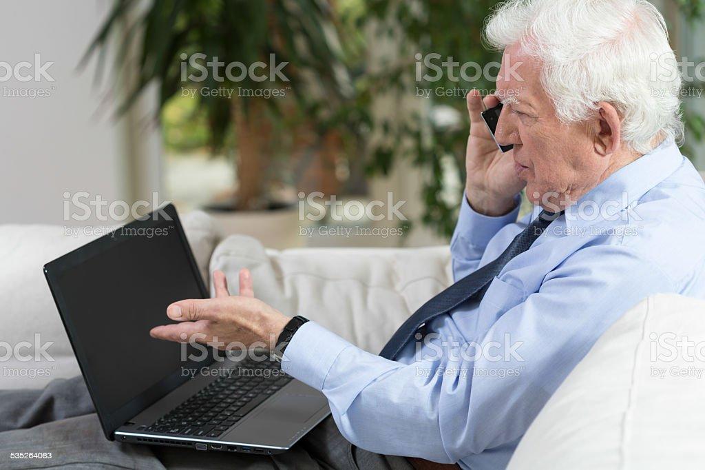 Senior businessman using laptop Senior businessman using laptop and talking on the phone 2015 Stock Photo