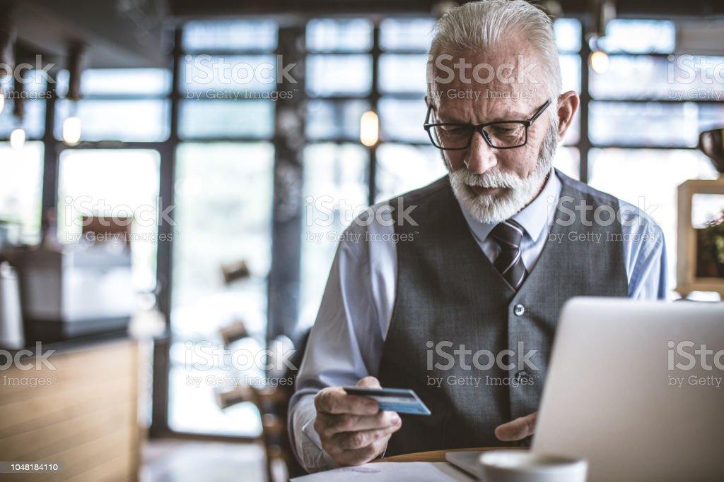 Senior businessman using laptop to check credit card . - Royalty-free Active Seniors Stock Photo
