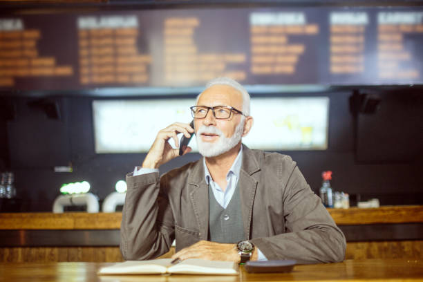 Senior businessman using mobile phone Active senior male person with eyeglasses in co-working space using mobile phone. old man working in a pub stock pictures, royalty-free photos & images