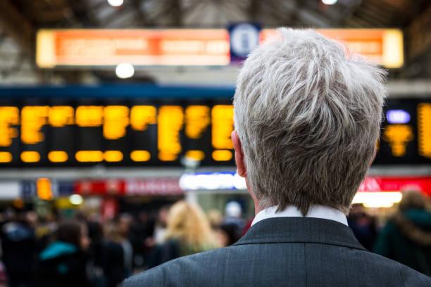 Homme d'affaires senior en attente pour le train avec les conseils de départ en arrière-plan, London, UK - Photo