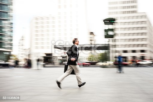 636248376istockphoto Senior businessman walking in the city streets 531535828