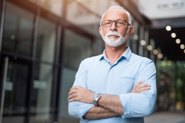Senior businessman with arms crossed looking at camera. stock photo