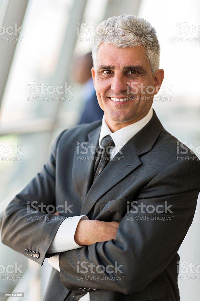 senior businessman with arms crossed stock photo