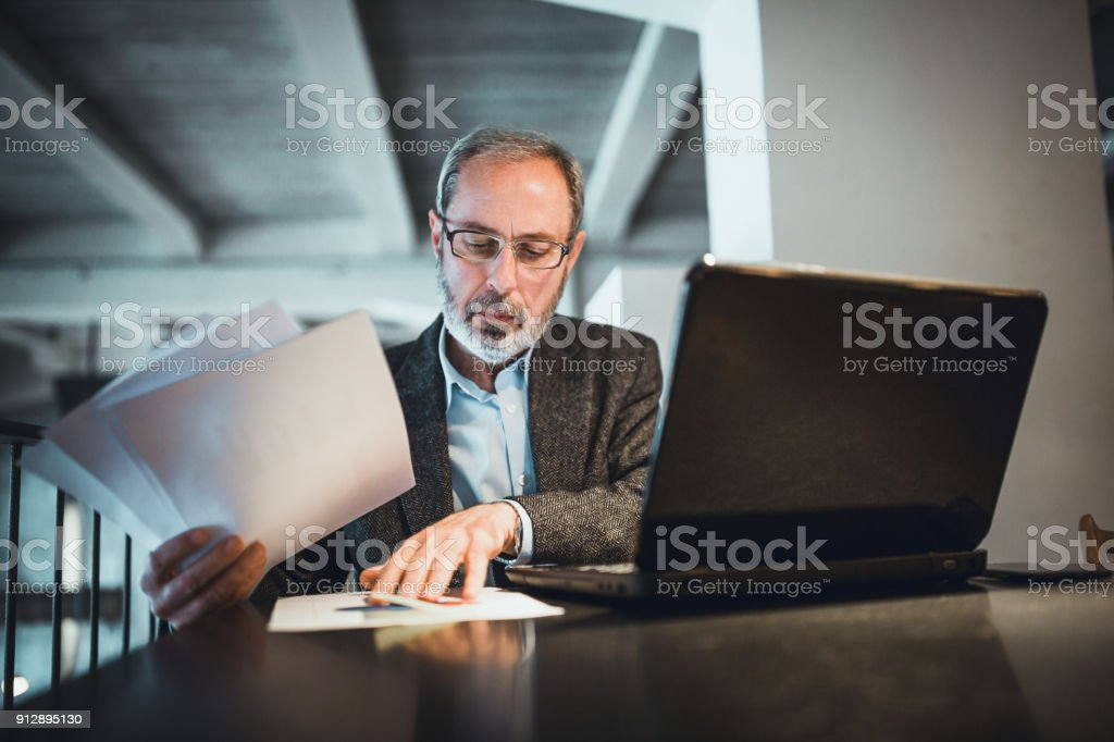 Senior businessman with beard working in high end restaurant, examining documents, using laptop stock photo