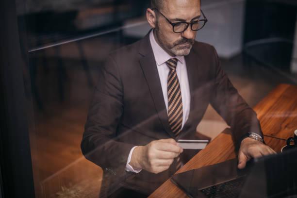 Senior businessman with eyeglasses shopping online stock photo