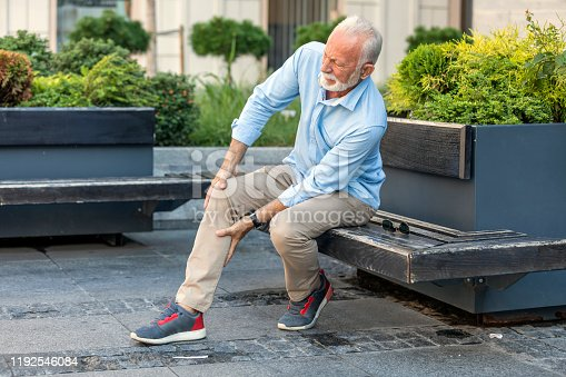 Mature Man with Grey Hair and Beard has Problems with his Knee in the City. Older Man is Sitting on the Wooden Bench in Public Park and Holding his Knee due to Physical Injury.