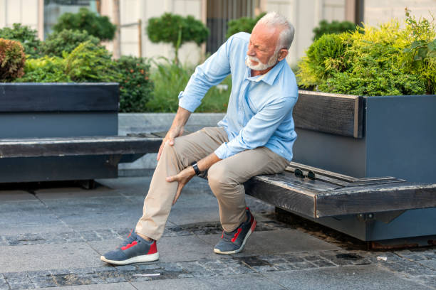 Senior Businessman with Knee Problems in the City Streets Mature Man with Grey Hair and Beard has Problems with his Knee in the City. Older Man is Sitting on the Wooden Bench in Public Park and Holding his Knee due to Physical Injury. cartilage stock pictures, royalty-free photos & images