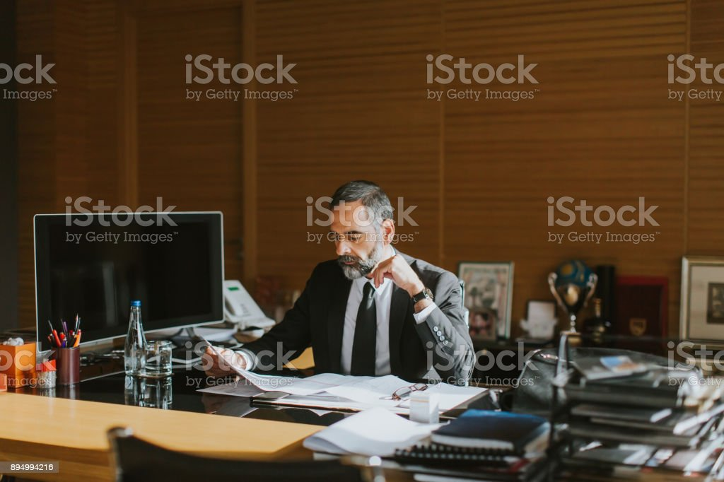 Senior businessman working on laptop in modern office stock photo