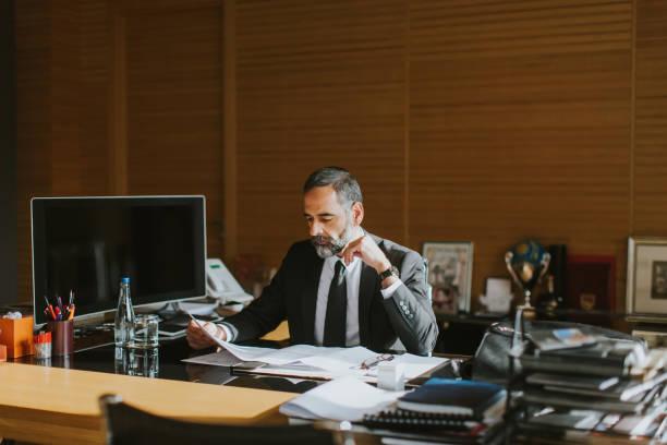 Homme d'affaires senior travaillant sur ordinateur portable au bureau moderne - Photo