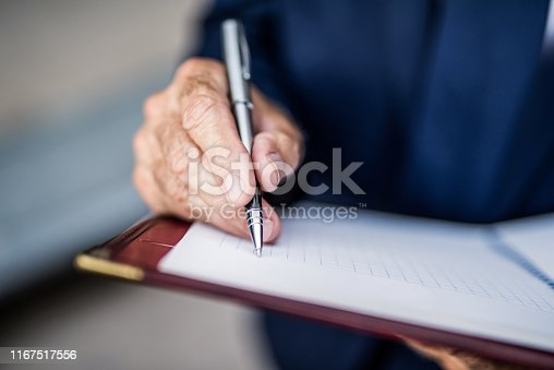 Senior businessman writing a business strategy in notebook.