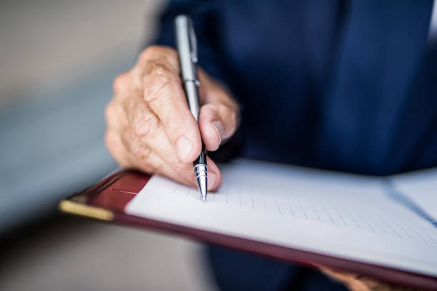 Senior businessman writing a business strategy in notebook. stock photo