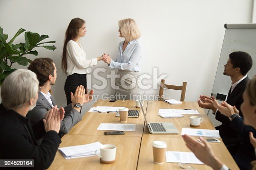 923041456 istock photo Senior businesswoman boss promoting thanking female employee while team applauding 924520164