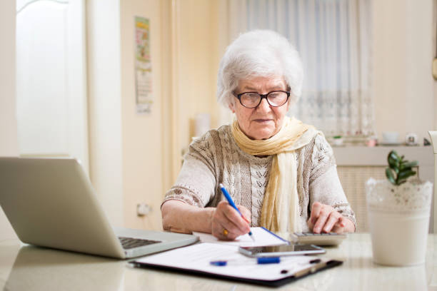 Senior businesswoman calculating taxes at home. stock photo