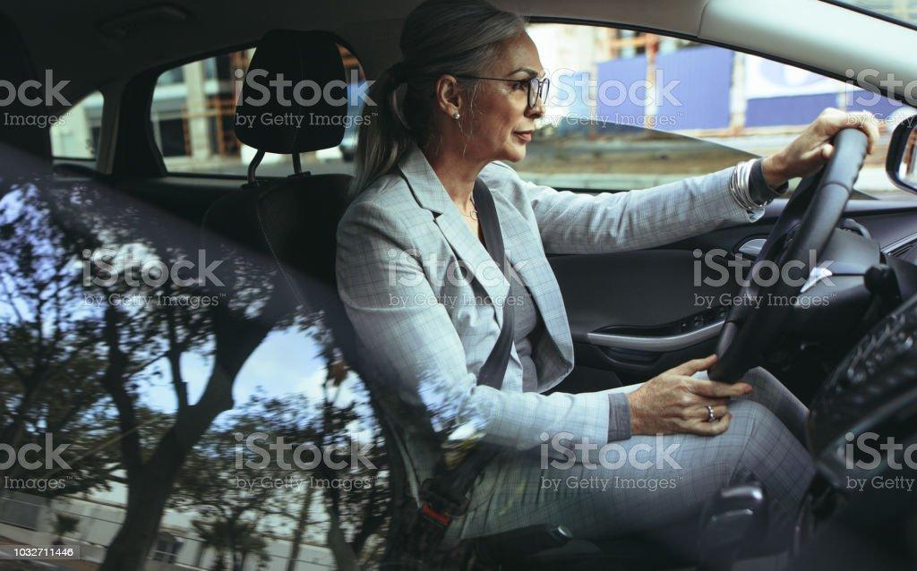 Empresaria Senior conduce a la oficina en un coche foto de stock libre de derechos