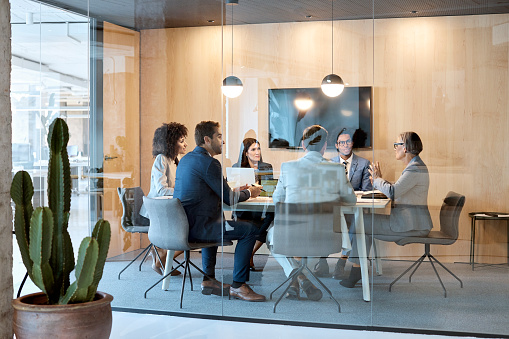 Senior businesswoman explaining strategy with colleagues in board room. Multi-ethnic professionals are discussing while sitting at desk in office. They are seen through glass.