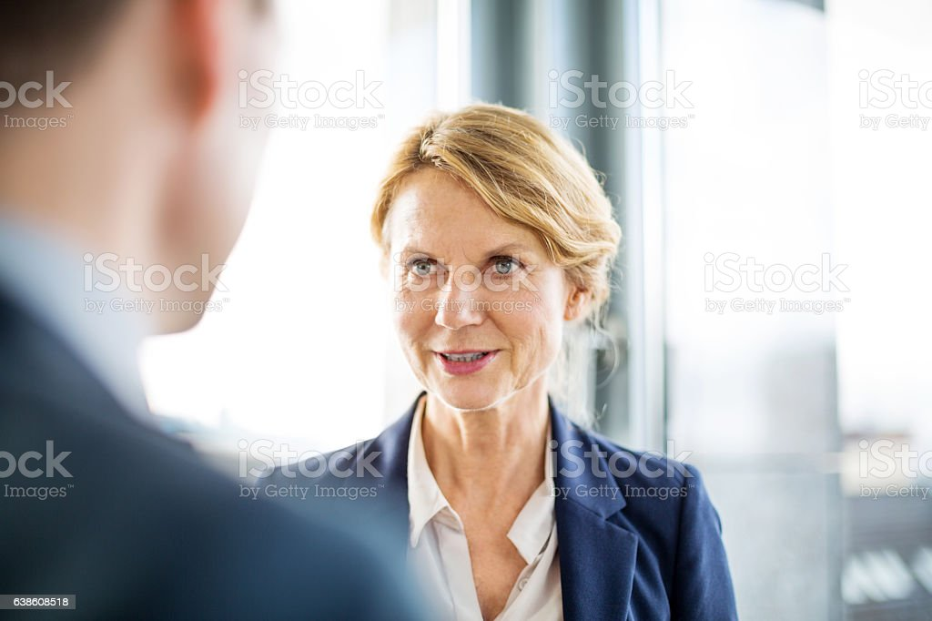 Senior businesswoman in discussion with colleague stock photo