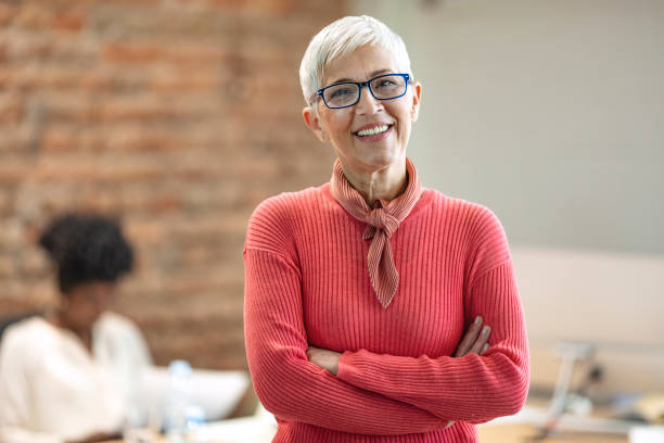 Senior Businesswoman In Office. Senior Businesswoman In Office. Pretty older business woman, successful confidence with arms crossed in financial building. Cheerful attractive businesswoman crossing arms on chest and looking at camera. professor stock pictures, royalty-free photos & images
