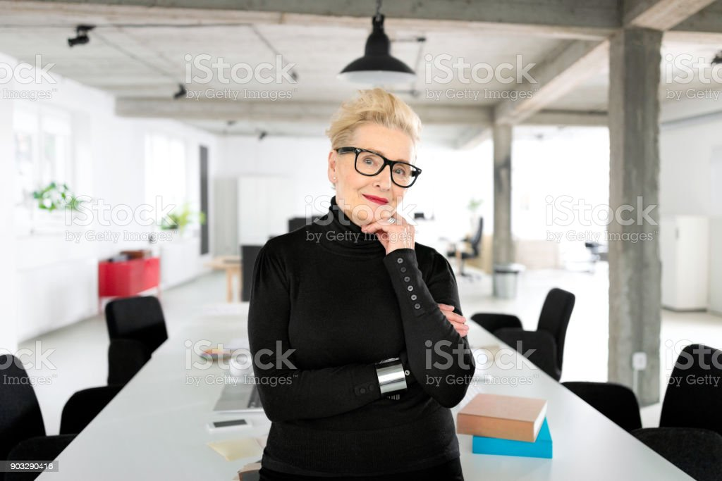 Senior businesswoman in the studio Portrait of senior elegant businesswoman standing in her office, smiling at the camera. 60-69 Years Stock Photo
