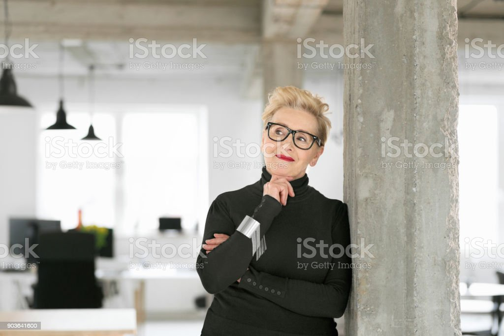 Senior businesswoman in the studio Portrait of senior elegant businesswoman standing in her office, smiling with hand on chin. 60-69 Years Stock Photo
