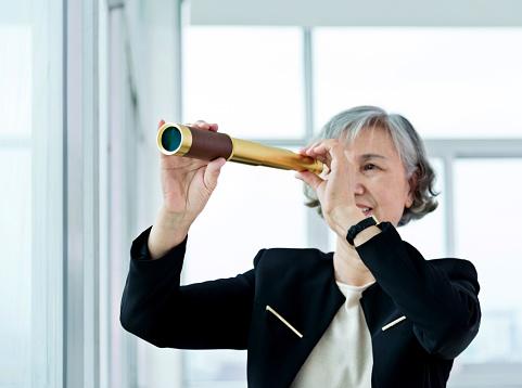 Senior businesswoman looking through telescope in office